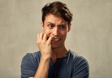Anxious man. Anxious nervous man portrait over gray wall background Royalty Free Stock Photo