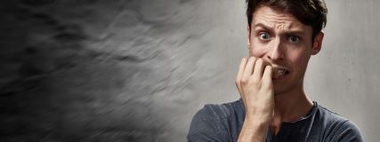 Anxious man. Anxious nervous man portrait over gray wall background Royalty Free Stock Photography