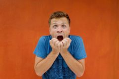 Anxious man is shocked and opening his mouth in surprise. On red background Stock Photography