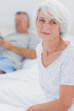 Anxious mature woman sitting in bed. Anxious mature women sitting in bed while husband is reading a newspaper on the background Royalty Free Stock Photos