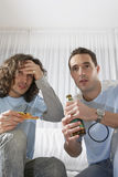 Anxious Men Watching TV And Having Pizza With Beer Stock Photo