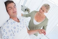 Anxious mother holding her sons hand. In hospital room Stock Photo