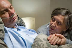 Anxious old woman taking care of husband Royalty Free Stock Images