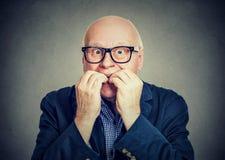 Anxious scared senior man biting fingernails. Anxious scared senior man in glasses biting fingernails Royalty Free Stock Photo