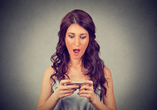 Anxious shocked girl looking at phone seeing bad news with stunned emotion on her face Royalty Free Stock Image