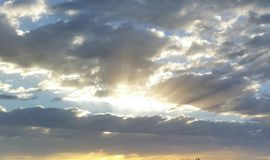 Anxious start to the day. The sun`s rays break like a fan through dense clouds, heralding the start of the day royalty free stock images