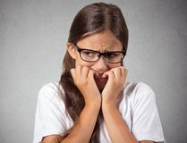 Anxious stressed teenager girl with eyeglasses biting fingernails Royalty Free Stock Image