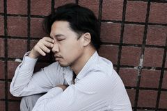 Anxious stressed young Asian business man suffering from severe depression. Thoughtful concept.  Stock Image