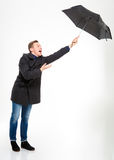 Anxious stressed young man with umbrella flying away. Anxious stressed young man in black coat and jeans with umbrella flying away over white background Royalty Free Stock Images