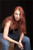 Anxious teen redhead seated Stock Images