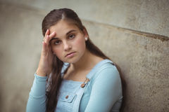 Anxious teenage girl leaning on wall. Portrait of anxious teenage girl leaning on wall at school stock images