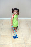 Anxious to Learn. Adorable little girl pushes her mop back and forth cleaning the floors.  She is learning household chores from her mom.  She is wearing a green Stock Photos