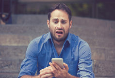 Anxious upset scared man looking at phone seeing bad news. Anxious upset young scared man looking at phone seeing bad news or text message sitting on stairs Royalty Free Stock Images