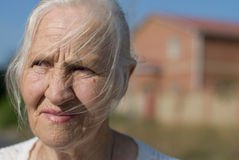 Anxious woman. Anxious elderly woman in crisis situation, building on the background Royalty Free Stock Photo