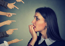 Anxious woman judged by different hands. Accusation of guilty girl Stock Image