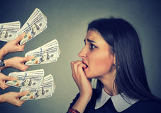 Anxious woman looking at money dollars offered by suspicious people. Anxious young woman looking at money dollar banknotes offered by suspicious people Royalty Free Stock Images