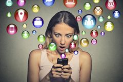 Anxious woman looking at smart phone app icons flying away from screen. Closeup portrait anxious young woman looking at smart phone multiple app icons flying Stock Photo