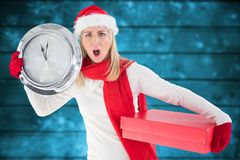 Anxious woman in santa hat holding a clock and christmas gift Royalty Free Stock Image