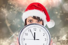 Anxious woman in santa hat holding a clock Stock Photography