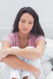 Anxious woman sat on her bed Royalty Free Stock Images