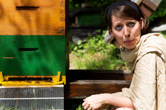 Anxious woman sitting on a beehive Royalty Free Stock Photos