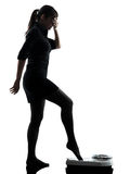Anxious woman standing on weight scale  silhouette Royalty Free Stock Photography