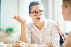 Anxious girl. Anxious women explaining reason of her worry to friend by cup of coffee Stock Photography