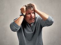 Anxious worried man. Anxious unhappy mature man portrait over gray background Stock Photography