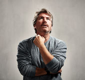 Anxious worried man. Anxious unhappy mature man portrait over gray background Royalty Free Stock Photo