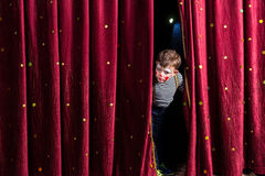 Anxious young actor looking out from the curtains. Anxious young boy actor in his costume and makeup looking out from the curtains on stage to check that Royalty Free Stock Photography