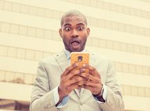 Anxious young business man looking at phone seeing bad news Royalty Free Stock Photos