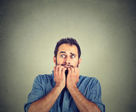 Anxious young man biting his nails fingers freaking out Royalty Free Stock Photography