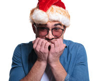 Anxious young man in santa hat Stock Images