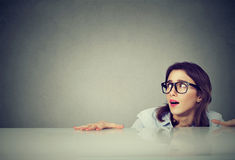 Free Anxious Young Woman Hiding Peeking From Under The Table Stock Photo - 97843120