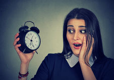 Anxious young woman looking at alarm clock. Time pressure concept Royalty Free Stock Images