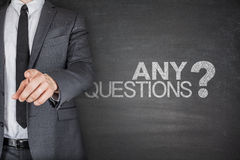Any Questions concept on black Blackboard. With businessman Stock Photography