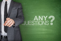 Any Questions concept on green Blackboard. With businessman Stock Photography