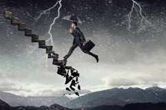 Any step maybe the last. Elegant businessman with suitcase and umbrella running up the stone falling staircase. Mixed media Stock Photo