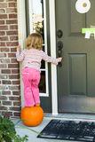 Anybody Home I'm Hoping to get some Candy Treat. Little toddler girl looking for Halloween candy on top of the pumpkin to reach the door bell while keeping Royalty Free Stock Photo