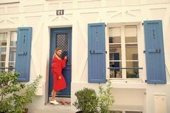Anybody home. Lady guest knocking door waits owner apartment let her enter. Woman stylish outfit stand near door. Entrance house picturesque street in Paris stock image