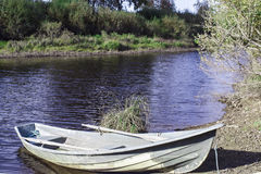 Anyone For A Boat Ride. A lonely boat at the river bench in the little town of Merijärvi, Finland royalty free stock image