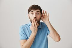 Anyone else know about this rumor. Portrait of shocked disbelieving male worker holding hands over mouth and near ear. While listening to gossip or overhearing Stock Photo
