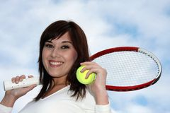 Anyone for tennis?. Pretty smiling tennis player with racket and ball Royalty Free Stock Photos