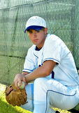 Anyone want to play baseball?. Young man sits on his heels waiting for someone to want to play baseball.  He has on a white and blue uniform Stock Photography