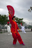 Anything can be used as a weapon. Chinese traditional martial art was more and more popular among ordinary citizens. People were practicing Taiji Fan in which Royalty Free Stock Photos
