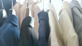Anzüge und Hemden auf einem Aufhänger stock video
