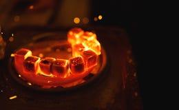 Anzünden der quadratischen Kohle für eine Huka auf einem speziellen Ofen mit einer heißen Spirale lizenzfreies stockbild