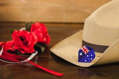 Anzac army slouch hat with Australian Flag. Anzac army slouch hat with red flower on vintage wood background Stock Photos