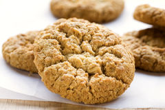 Anzac Biscuit close-up. Close-up view of an Anzac biscuit on baking paper with other biscuits in the background stock image
