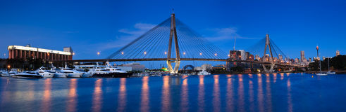 Anzac bridge 45 pan. Anzac bridge panoramic view at sunset with beauty lights illumination and reflection in harbour water with boats royalty free stock image